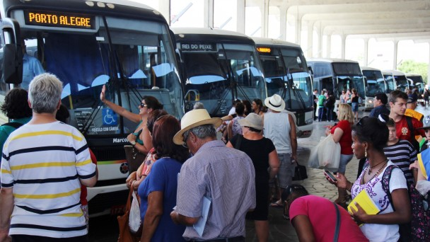 A foto mostra um grande número de passageiros aguardando o embarque dos ônibus na rodoviária de Porto Alegre. Os veículos estão todos estacionados.